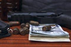 På tabelllögnen en pistol, pengar, ammunition, en handväska royaltyfri fotografi