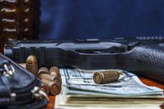 På tabelllögnen en pistol, pengar, ammunition, en handväska arkivbilder