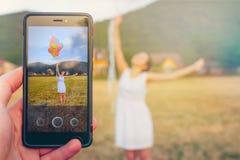 På telefonen fotograferade en ung kvinna med ballonger i hennes händer Begreppet av kreativitet och modern teknologi royaltyfria foton