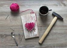 På trälögner för en tabell spikar spikar en hammare en kopp av trådrosa färger och en gåva av din egen hjärta en hjärta av trådar Royaltyfri Foto