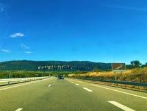 På vägen: berg, himmel och gatan fotografering för bildbyråer
