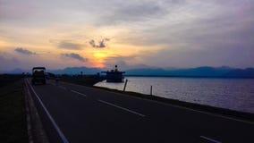 På vägen, floden och den härliga solnedgången royaltyfri fotografi