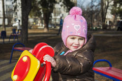 På våren av lekplatsen är en att le liten flicka Arkivbilder