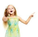 På vitbakgrund pekar en liten flicka ett finger Royaltyfria Bilder