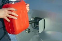 Påfyllning av bilen med bränsle från kanistern royaltyfri foto