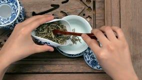 Påfyllning av en brun tekanna till och med en tratt Porslinkineskoppar, ståltesked Svärta, göra grön, puerh, oolong, tieguanyin Arkivfoto