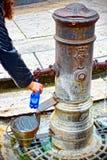 Påfyllning av en vattenflaska på en dricka springbrunn i Rome royaltyfri fotografi