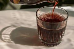 Påfyllning av ett exponeringsglas av granatäpplefruktsaft Arkivfoto