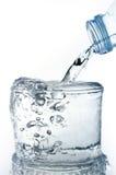 Påfyllning av ett exponeringsglas med vatten som visar ett drinkbegrepp Royaltyfri Foto