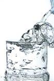 Påfyllning av ett exponeringsglas med vatten som visar ett drinkbegrepp Royaltyfri Fotografi