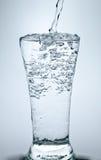 Påfyllning av ett exponeringsglas med vatten som visar ett drinkbegrepp Arkivbilder