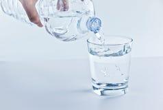 Påfyllning av ett exponeringsglas med vatten till och med flask-, näring- och sjukvårdbegrepp arkivbilder