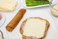 Påfyllning av quinoakräpparna med ost och skinka Arkivbild