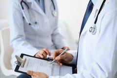 Påfyllning för två medicinsk form för okänd doktorer på skrivplattan, precis handcloseup Läkare som frågar fråga till patienten e arkivbild