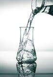 Påfyllning i konisk flaska med vatten Fotografering för Bildbyråer