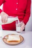 Påfyllningen mjölkar in i ett exponeringsglas Arkivbild