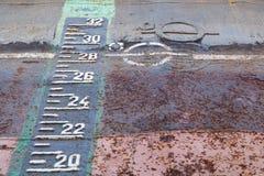 Påfyllninglinje markering och utkastskala på den rostiga skrovet av skeppet i torr anslutning under reparationer royaltyfri foto