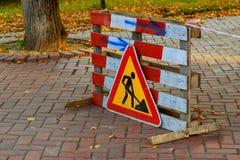 Pågående arbete Roadworks vägmärken Män på arbete Någon teckensignage för arbete som är pågående på den stads- gatan Royaltyfri Foto