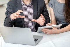 Pågående arbete Unga businesspeople som sitter på tabellen och Arkivbilder