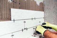 Pågående renovering Industriarbetare som installerar badrumtegelplattor royaltyfria foton