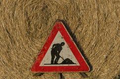 Pågående roadsign för arbete över sugrörrundabalen Arkivfoto