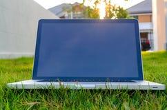 Pålagd datoranteckningsbok gräset Arkivfoto