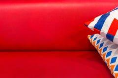 Pålagd röd lyxig soffa för färgrik kudde för modern design Härligt garneringhusobjekt av kopplar av eller vilar royaltyfria bilder