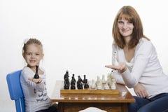 Pålagda mamma och dotter gömma i handflatan av Queens som spelar schack Royaltyfri Foto