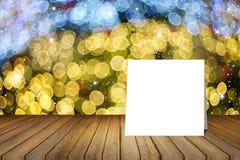 Pålagt träskrivbord för vitt kort mot suddigt abstrakt begrepp ut ur bakgrund för fokusbokehljus bruk för gåva eller åtlöje upp d Royaltyfri Foto