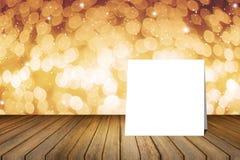 Pålagt träskrivbord för vitt kort mot suddigt abstrakt begrepp ut ur bakgrund för fokusbokehljus bruk för gåva eller åtlöje upp d Arkivfoton