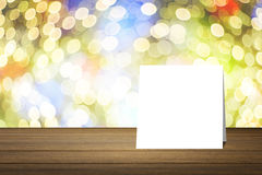 Pålagt träskrivbord för vitt kort mot suddigt abstrakt begrepp ut ur bakgrund för fokusbokehljus bruk för gåva eller åtlöje upp d Arkivbilder