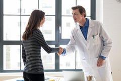 Pålitlig läkare- och kvinnligpatient som skakar händer för konsultation arkivfoto