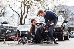 Pålitlig ung man som hjälper en sårad kvinna, medan vänta på ambulansen royaltyfri fotografi