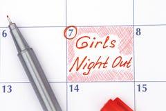 Påminnelseflickanatt ut i kalender med pennan royaltyfri bild