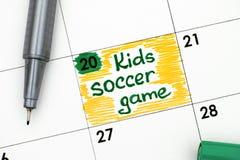 Påminnelsen lurar fotbollleken i kalender med pennan Royaltyfri Foto