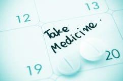 Påminnelsen tar medicin på kalender royaltyfri fotografi