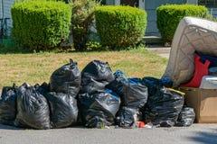 Påsar av avskräde på trottoarkanten Royaltyfri Foto