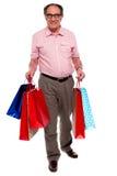 påsar som bär lycklig man mognad shopping Arkivfoto