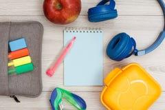 Påse-blyertspenna fall med färgfiltpennor och den markör-, äpple-, anteckningsbok-, hörlurar-, häft- och lunchasken royaltyfria bilder