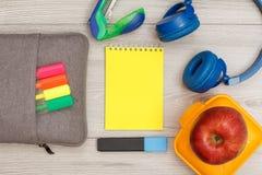 Påse-blyertspenna fall med färgfiltpennor och den markör-, anteckningsbok-, hörlurar-, häft-, äpple- och lunchasken royaltyfria bilder