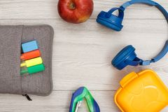 Påse-blyertspenna fall med färgfiltpennor och markör, äpple, häftapparat, hörlurar och lunchask royaltyfri fotografi