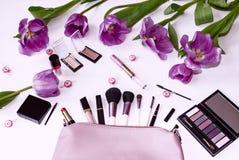 Påse för kosmetiska borstar, dekorativa skönhetsmedel och tulpanblommor fotografering för bildbyråer