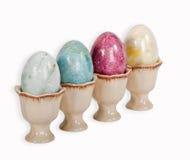 Påskägg i äggkoppar över vit Arkivfoto
