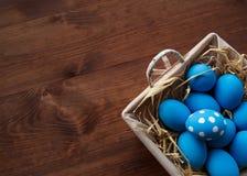 Påskägg i en korg på lantlig träbakgrund, bild för selektiv fokus, lycklig påsk Arkivbild