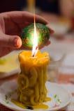 Påskägg i förlagehänderna ovanför stearinljuset Arkivfoton
