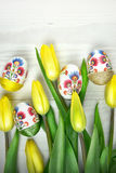 Påskägg i handen - gjord decoupagegarnering med gula tulpan Fotografering för Bildbyråer