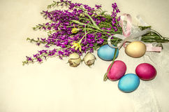 Påskägg nära buketten av purpurfärgade lösa blommor som in slås in, snör åt bandet Royaltyfri Fotografi
