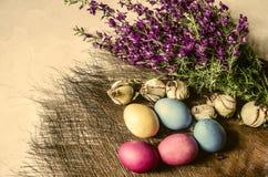Påskägg nära en bukett av blommande purpurfärgade lösa blommor Arkivfoto