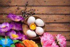 Påskägg och blommor på träbräden, konstgjorda blommor och dekorativa ägg från trä, Arkivbild