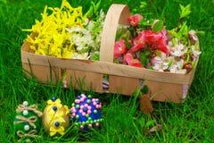 Påskägg och en korg med blommor Arkivfoton